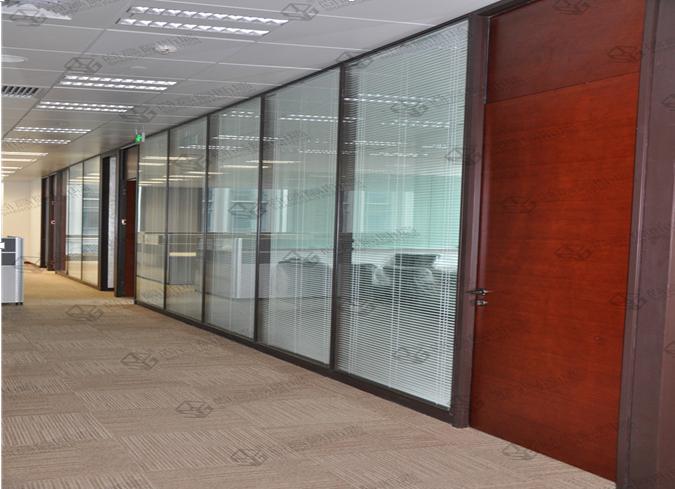 设计合理的办公室玻璃隔断具有保温的功能,办公室的空间很大,利用尚高隔断墙品牌成品玻璃隔断相对自由地合理隔断空间,目前日益流行的办公室玻璃隔断分类款式有铝合金玻璃隔断、防火玻璃隔断、不锈钢玻璃隔断等,有利于保持办公工作区域的温度。  办公室玻璃隔断效果图(100%实景) 装修办公室玻璃隔断已经是一种十分流行和普遍的了,办公室玻璃隔断技术日益完善,铝合金百叶玻璃隔断产品款式也在不断更新,功能和装饰效果都已经非常好的。